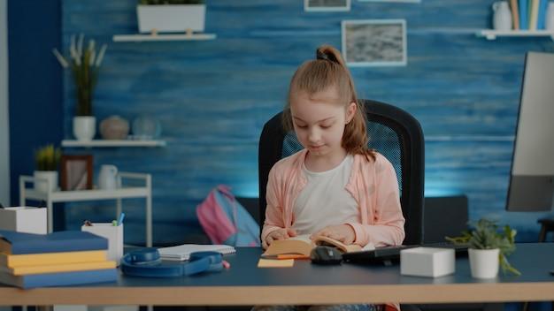 Małe dziecko otwiera książkę i czyta na zajęcia szkolne