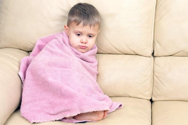 Małe dziecko owinięte w ręcznik po kąpieli. domowy odpoczynek dziecka po zabiegach wodnych