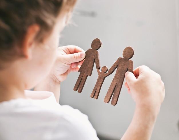 Małe dziecko patrząc na drewniane postacie mamy, taty i dziecka w dłoniach. koncepcja dziecka marzącego o rodzinie