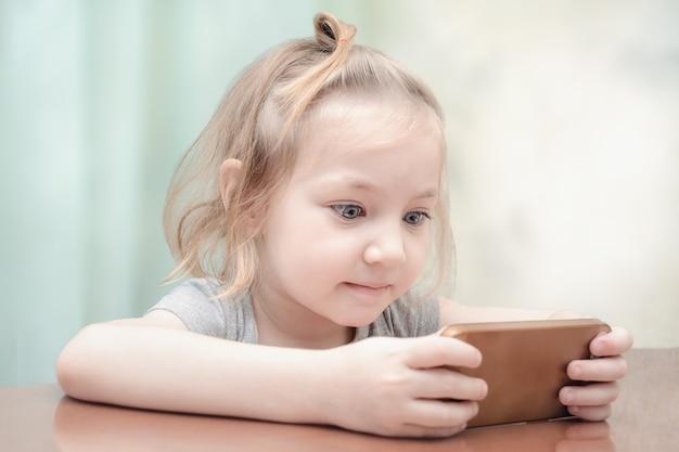 Małe dziecko patrzy na telefon ze zdziwieniem.