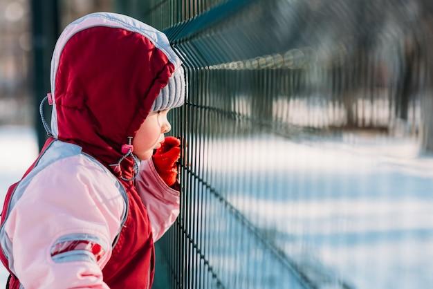 Małe dziecko patrzy zimą przez kraty