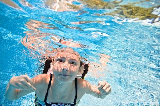 Małe dziecko pływa pod wodą w basenie, szczęśliwa aktywna dziewczynka nurkuje i bawi się pod wodą, fitness dla dzieci i sport