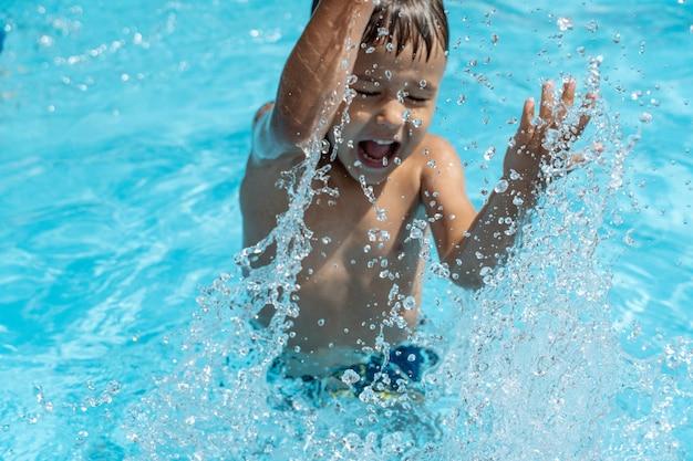 Małe dziecko pływa w basenie, bawi się pluskającą wodą
