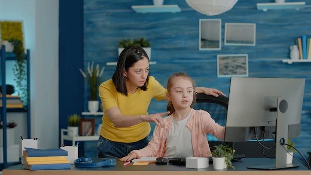 Małe dziecko prosi matkę o pomoc przy pracy z komputerem