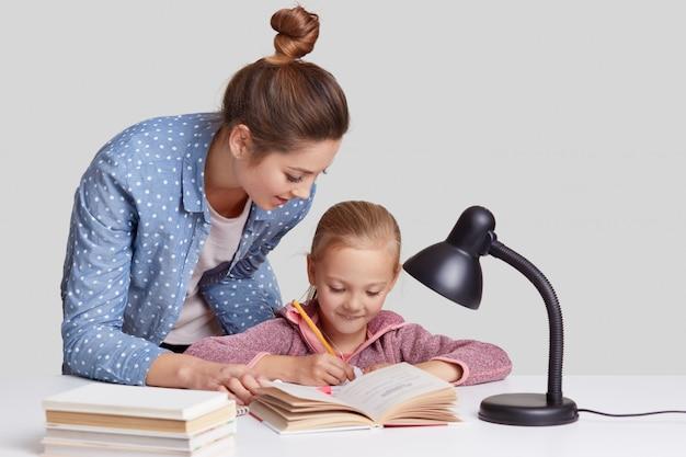 Małe dziecko przepisuje informacje w zeszycie, ma zadowoloną minę, jej matka stoi blisko, próbuje zachęcić córkę do nauki, pomaga i wyjaśnia materiał, na białym tle