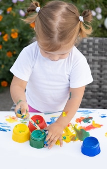 Małe dziecko rysunek farbą i pędzlem. cute little girl malowanie obrazu w ogrodzie, na zewnątrz w domu, na podwórku