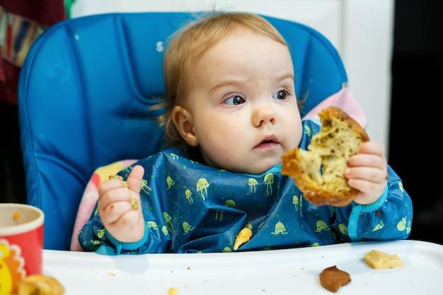 Małe dziecko siada na krzesełku do karmienia i po raz pierwszy je chleb. twarz w okruchach