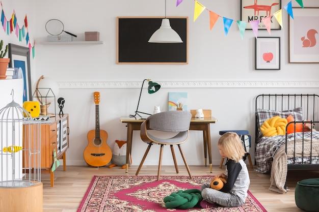 Małe dziecko siedzące na dywanie w białej sypialni z zabytkowymi meblami