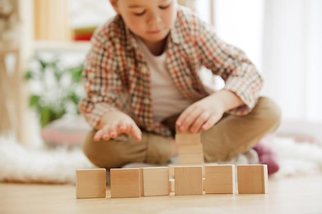 Małe dziecko siedzi na podłodze. ładny chłopak palying z drewnianymi kostkami w domu. obraz koncepcyjny z miejsca kopiowania lub negatywu i makiety tekstu