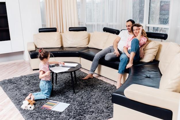 Małe dziecko siedzi na podłodze w salonie i maluje ołówkami, podczas gdy rodzice odpoczywają na kanapie