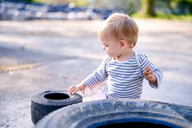 Małe dziecko siedzi przy oponach samochodowych na parkingu