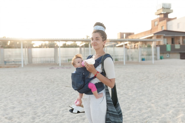 Małe dziecko siedzi w plecaku i idzie wraz z matką wzdłuż brzegu morza.