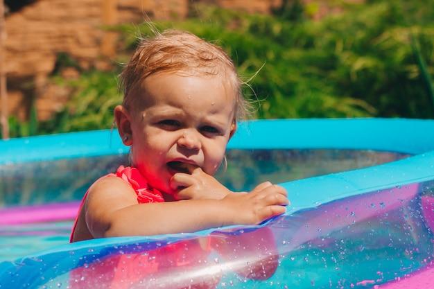 Małe dziecko sięga do ust z palcami i rosną zębami