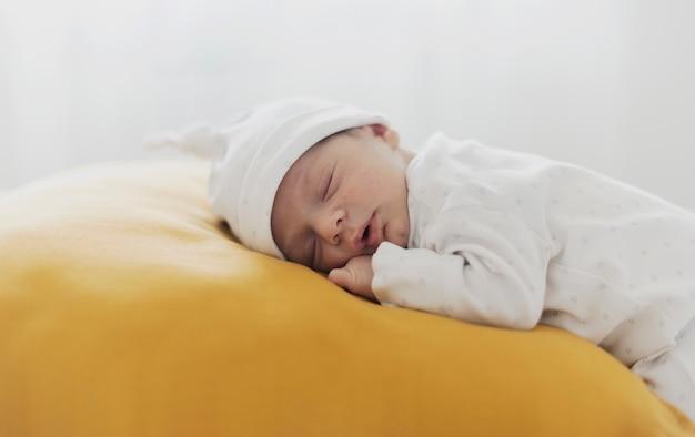 Małe dziecko śpi na żółtej poduszce