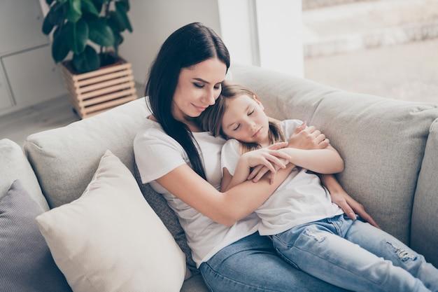 Małe dziecko śpi obok matki na wygodnej kanapie w domu w pomieszczeniu