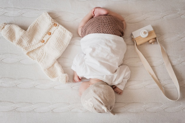 Małe dziecko śpi obok zimowego swetra