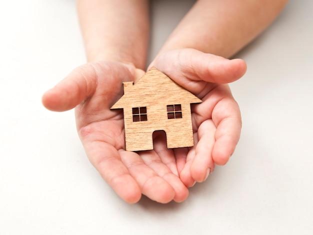 Małe dziecko trzyma drewniany dom płaski w rękach na białym tle