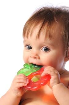 Małe dziecko trzyma kolorową zabawkę ząbkowanie