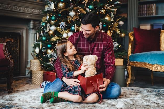 Małe dziecko trzyma misia, otrzymuje nieoczekiwany prezent od czułego ojca, będąc mu wdzięcznym