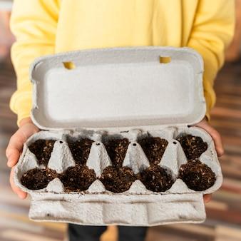 Małe dziecko trzyma posadzone nasiona w kartonie jaj