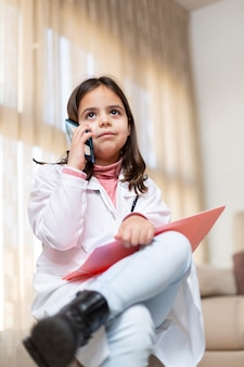 Małe dziecko ubrane w mundur pielęgniarki rozmawia przez telefon komórkowy