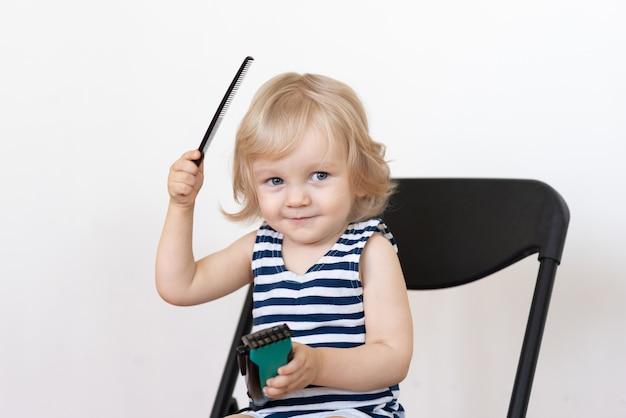 Małe dziecko uczy się obcinać włosy i czesać je
