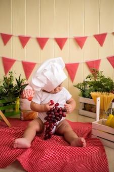 Małe dziecko w białej czapce szefa kuchni trzyma winogrona