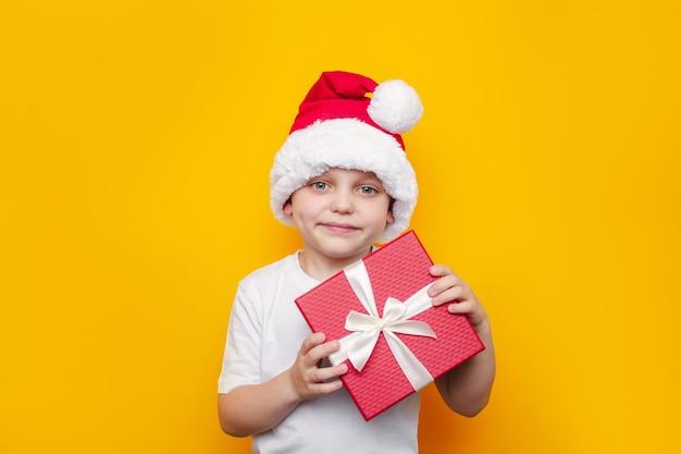 Małe dziecko w białej koszulce i czerwonej czapce mikołaja trzyma pudełko z białą wstążką i kokardą