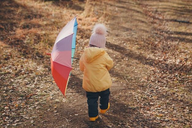 Małe dziecko w ciepłym garniturze z kolorowym parasolem spaceruje po lesie. park jesień. koncepcja mody dziecięcej, akcesoriów, spacerów na świeżym powietrzu