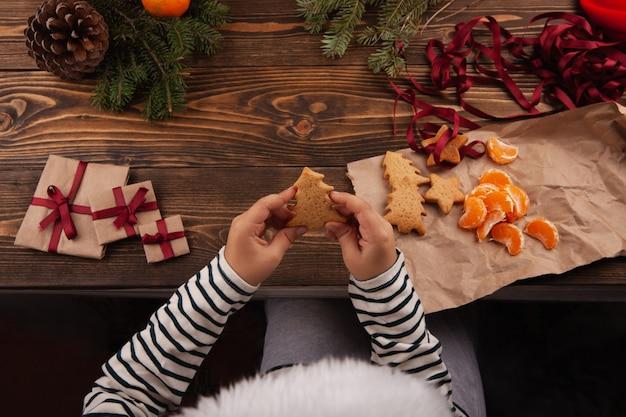 Małe dziecko w czapce świętego mikołaja siedzi przy stole i trzyma w rękach świąteczne ciasteczka.