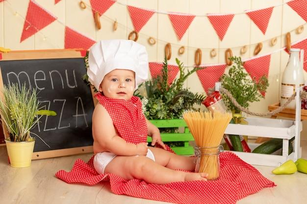 Małe dziecko w czapce szefa kuchni gotuje spaghetti w kuchni