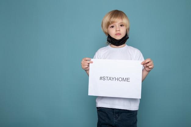 Małe dziecko w czarnej masce ochronnej z białą koszulką i niebieskimi jeansami z haftowanym hashtagiem na tle niebieskiego biurka