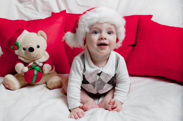 Małe dziecko w czerwonej czapce zjada ciasteczka i mleko. świąteczna fotografia dziecka w czerwonej czapce. święta nowego roku i boże narodzenie.
