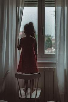 Małe dziecko w czerwonej sukience patrząc przez okno w deszczowy dzień