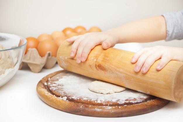 Małe dziecko w domowej kuchni przygotowujące ciasto na pizzę lub inne jedzenie.