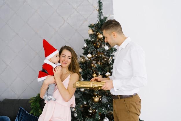 Małe dziecko w garniturze świętego mikołaja w ramionach matki w pobliżu choinki, tata daje mamie i dziecku prezent na nowy rok. dzieciak patrzy na ojca ze zdziwieniem