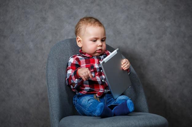 Małe dziecko w koszuli bawi się tabletem