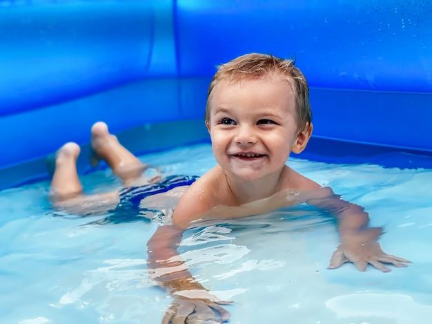 Małe dziecko w nadmuchiwanym okrągłym basenie dla dzieci w słoneczną letnią pogodę. koncepcja lato i wakacje.