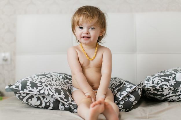Małe dziecko w pieluszce leży na łóżku i się śmieje