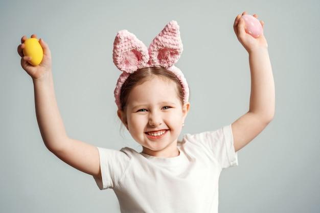 Małe dziecko w różowej pałąk uszy królika gospodarstwa pisanki.