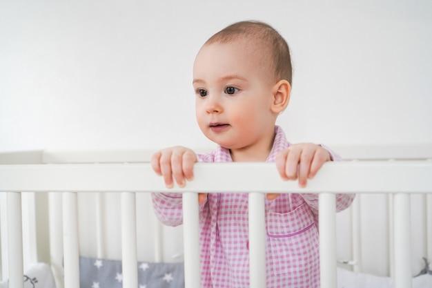 Małe dziecko w różowej piżamie stoi w łóżeczku. dzieciak obudził się i czeka, aż jego rodzice wyciągną go z łóżeczka.