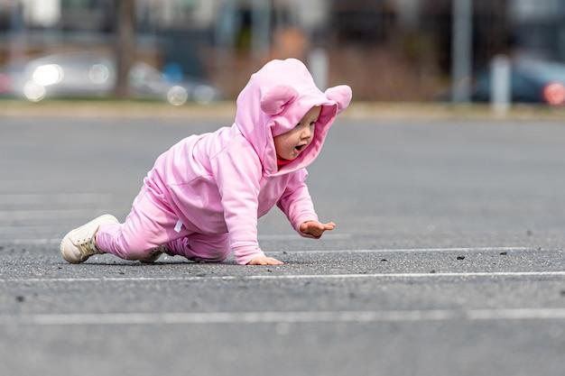 Małe dziecko w różowej sukience czołgające się po asfalcie na parkingu samochodowym