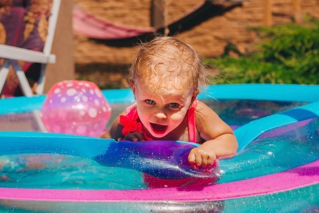 Małe dziecko w różowym kostiumie kąpielowym na jedno ramię pływa w nadmuchiwanym basenie na podwórku
