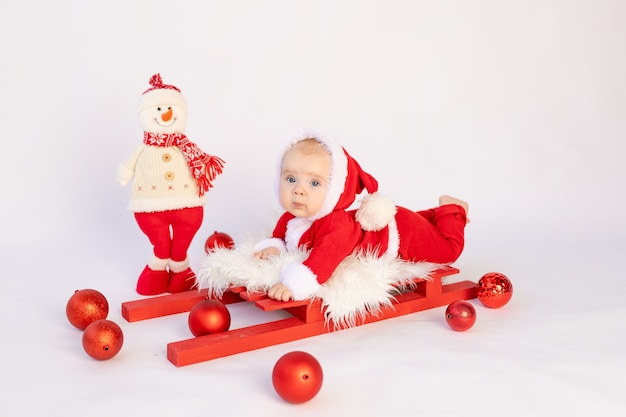 Małe dziecko w stroju świętego mikołaja leży na saniach na białym tle