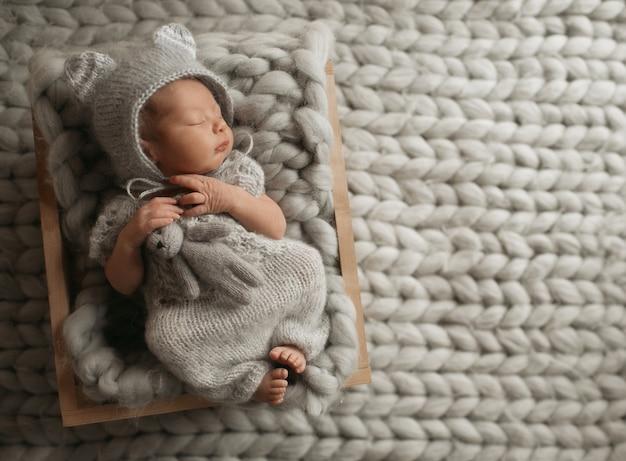 Małe dziecko w szarych ubraniach śpi na wełnianym kocu