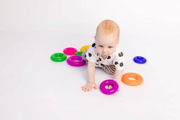 Małe dziecko w wieku 8 miesięcy czołga się na białym tle z zabawkami, miejscem na tekst