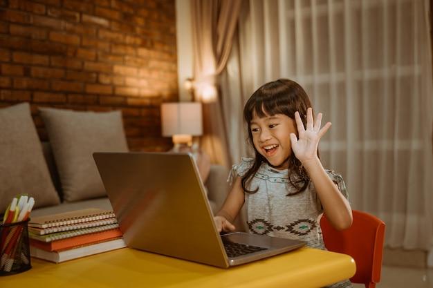 Małe dziecko wideo dzwoni używać laptop w domu w wieczór