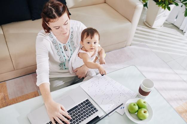 Małe dziecko wskazujące na raport matki pracującej na laptopie w domu, widok z góry