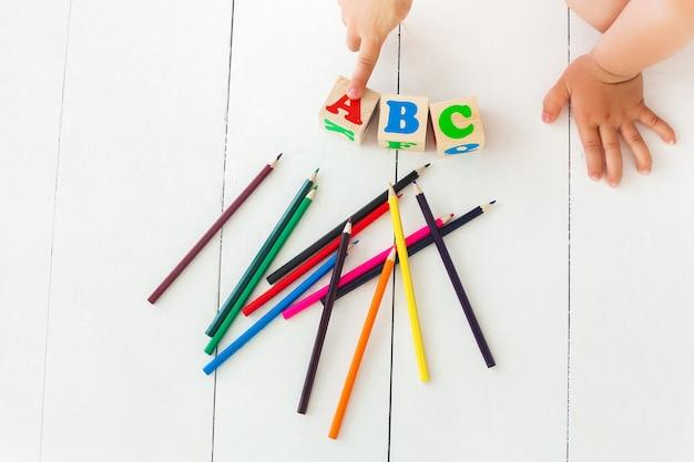 Małe dziecko wskazuje kostki abc. alfabet tło cegły abc na neutralnym tle. kolorowe ołówki