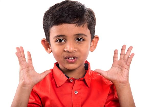 Małe dziecko wydaje zdziwione lub szokujące miny na białej ścianie